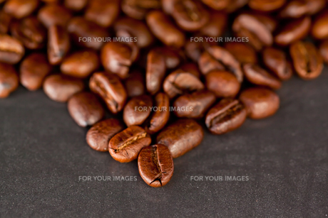 Blurred coffee seeds laid out together on a black tableの写真素材 [FYI00487040]