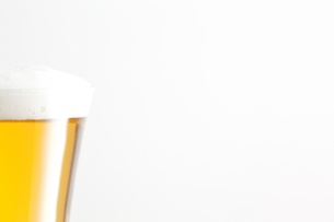 Glass of beer and foam against a white backgroundの写真素材 [FYI00487069]