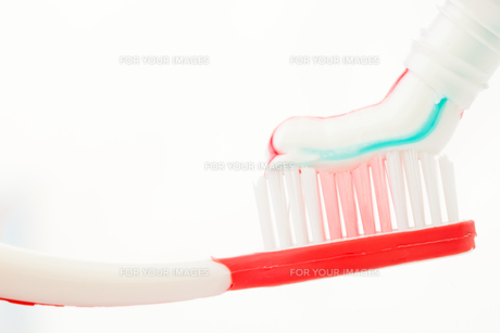 Red toothbrush with multicolour toothpasteの写真素材 [FYI00487093]