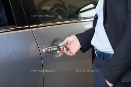 Man opening a car door with a keyの写真素材 [FYI00487096]