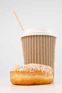 A multi coloured doughnut and a cup of tea placed togetherの写真素材 [FYI00487097]