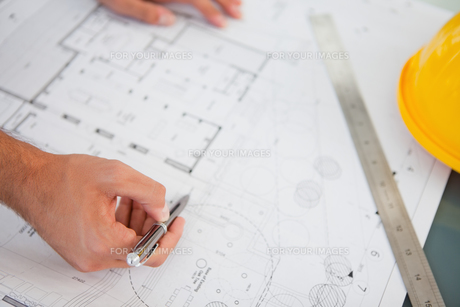 Close up of blueprints with a person making adjustmentsの素材 [FYI00487118]