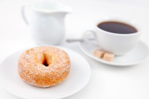 Doughnut with icing sugar and a cup of coffee on white plates with sugar and milkの写真素材 [FYI00487153]