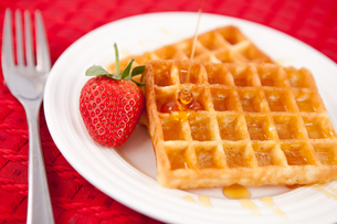 Waffles and syrup and strawberry together in a white plateの写真素材 [FYI00487156]