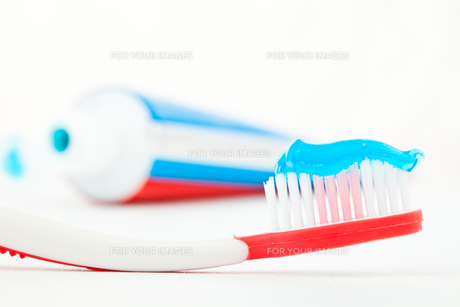 Tube of toothpaste next to a red toothbrushの写真素材 [FYI00487181]