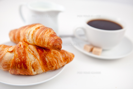 Two croissants and a cup of coffee on white plates with sugar and milkの写真素材 [FYI00487226]