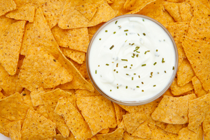 Bowl of dip with herbs surrounded by nachosの写真素材 [FYI00487229]