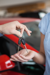 Car keys hold by someone over someone else handの素材 [FYI00487241]