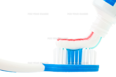 Close up of a tube of toothpaste with a toothbrushの写真素材 [FYI00487275]