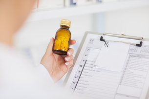Pharmacist holding a drug bottle and a clipboardの写真素材 [FYI00487292]