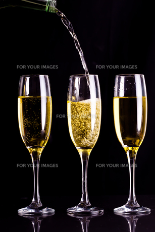 Two full glasses of champagne and one being filledの写真素材 [FYI00487295]