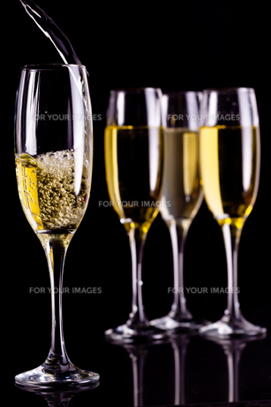 Full glasses of champagne and one being filledの写真素材 [FYI00487313]
