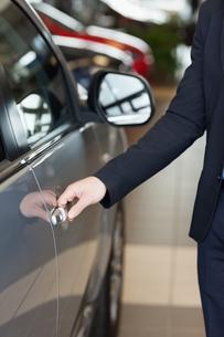 Man holding a car door handlesの写真素材 [FYI00487338]