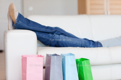 Female legs resting on sofa after shopping tourの写真素材 [FYI00487347]