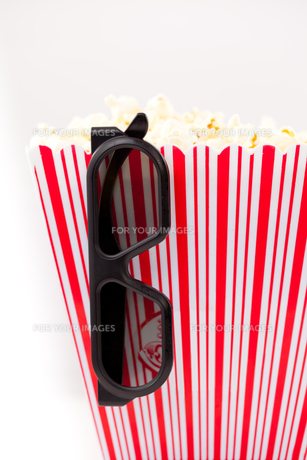 Glasses hanging on a box full of popcornの素材 [FYI00487380]