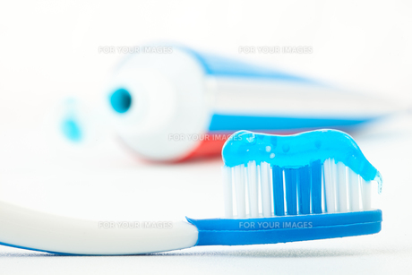 Toothbrush with blue toothpaste next to a tube of toothpasteの素材 [FYI00487387]