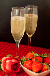 Top glasses of champagne with strawberries in a bowl and a rose on a red tableclothの素材 [FYI00487399]