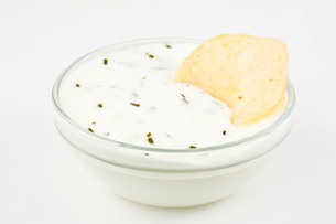 Bowl of white dip with herbs and a nacho dipped in itの写真素材 [FYI00487452]