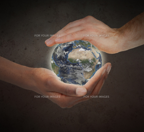 Two hands protecting a glowing planet globeの写真素材 [FYI00487480]