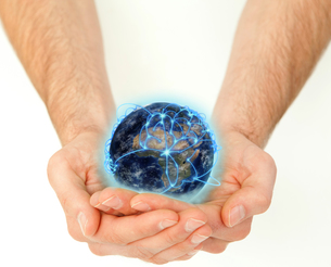 Masculine hands holding a connected planet globeの写真素材 [FYI00487491]