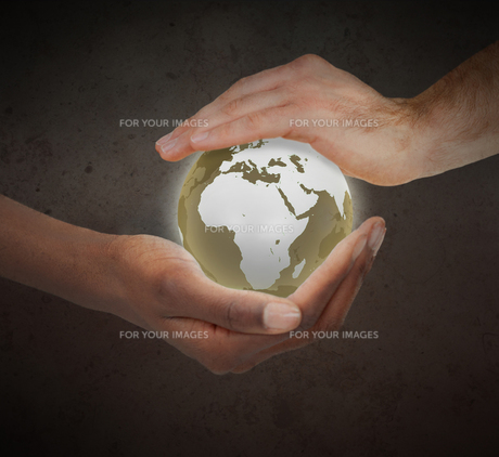 Hands protecting a glowing planet globeの写真素材 [FYI00487492]