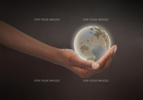 Feminine hand holding a glowing planet globeの写真素材 [FYI00487498]