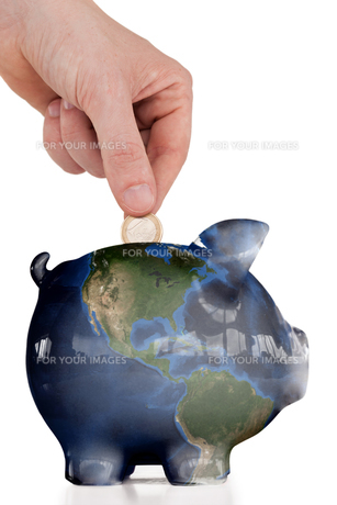 Hand inserting a coin in a piggy bankの写真素材 [FYI00487504]