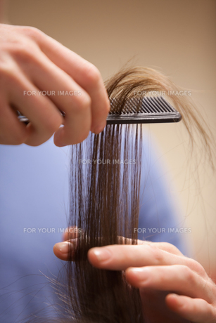 Close up of a hand combing hairの素材 [FYI00487509]