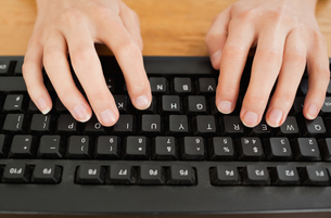 Typing woman on keyboardの写真素材 [FYI00487515]