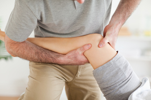 Chiropractor massaging a patients kneeの素材 [FYI00487527]