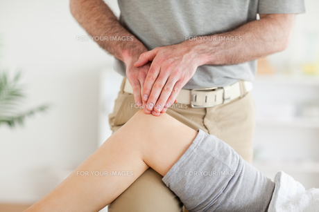 Chiropractor massaging a cute womans kneeの素材 [FYI00487544]