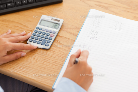 Feminine hands using a calculator and a penの写真素材 [FYI00487550]