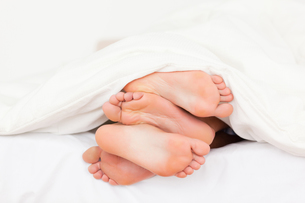 Stack of feet in a bedの写真素材 [FYI00487571]