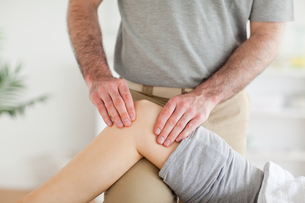 Male Chiropractor massaging a charming womans kneeの素材 [FYI00487593]