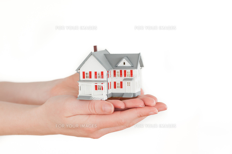 Hands holding a miniature house on a white backgroundの写真素材 [FYI00487631]