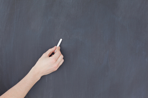 Hand holding a chalk and and ready to write on a blackboardの写真素材 [FYI00487639]