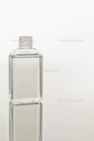 Glass flask on a mirror against white backgroundの素材 [FYI00487663]