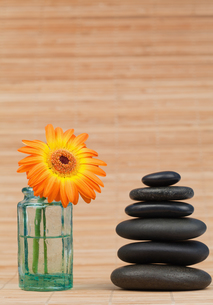 Orange snflower in a glass flask beside a black stones stackの写真素材 [FYI00487710]
