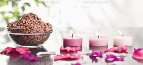 Pink petals with lighted candles and a bowl of brown gravelの写真素材 [FYI00487719]