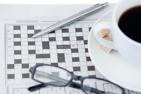 A cup of coffee a pen a pair of glasses and a crossword puzzleの写真素材 [FYI00487731]