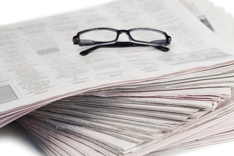 A pair of glasses on a pile of newspapersの素材 [FYI00487769]