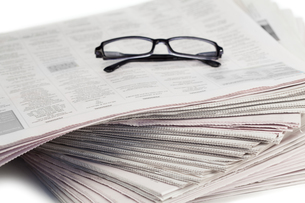 A pair of glasses on a pile of newspapersの写真素材 [FYI00487769]