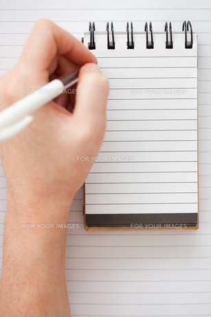 Woman hands writing on a notebookの写真素材 [FYI00487779]
