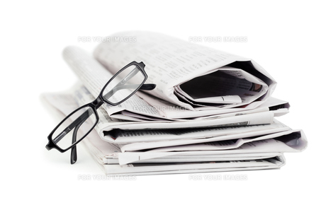 A pile of newspapers and a pair of reading glassesの素材 [FYI00487811]