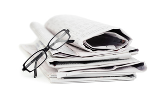 A pile of newspapers and a pair of reading glassesの写真素材 [FYI00487811]