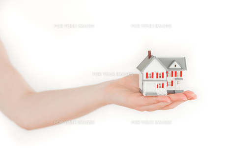 Arm holding a miniature house on a white backgroundの写真素材 [FYI00487818]