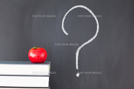 Stack of books with a red apple and a blackboard with a question mark symbolの写真素材 [FYI00487824]