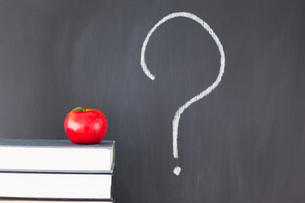 Stack of books with a red apple and a blackboard with a question mark symbolの素材 [FYI00487824]