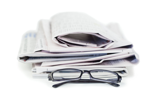 A pile of newspapers and a pair of reading glassesの写真素材 [FYI00487839]
