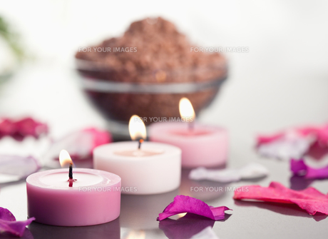 Close up of lighted candles with a brown gravel bowl and petalsの素材 [FYI00487869]